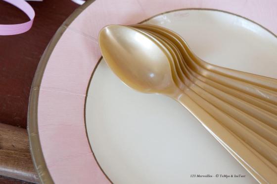 Assiette rose poudré et cuillères dorées